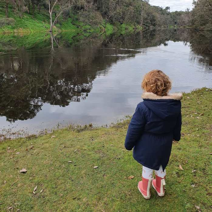 Small girl wearing raincoat and gumboots, standing by a pond