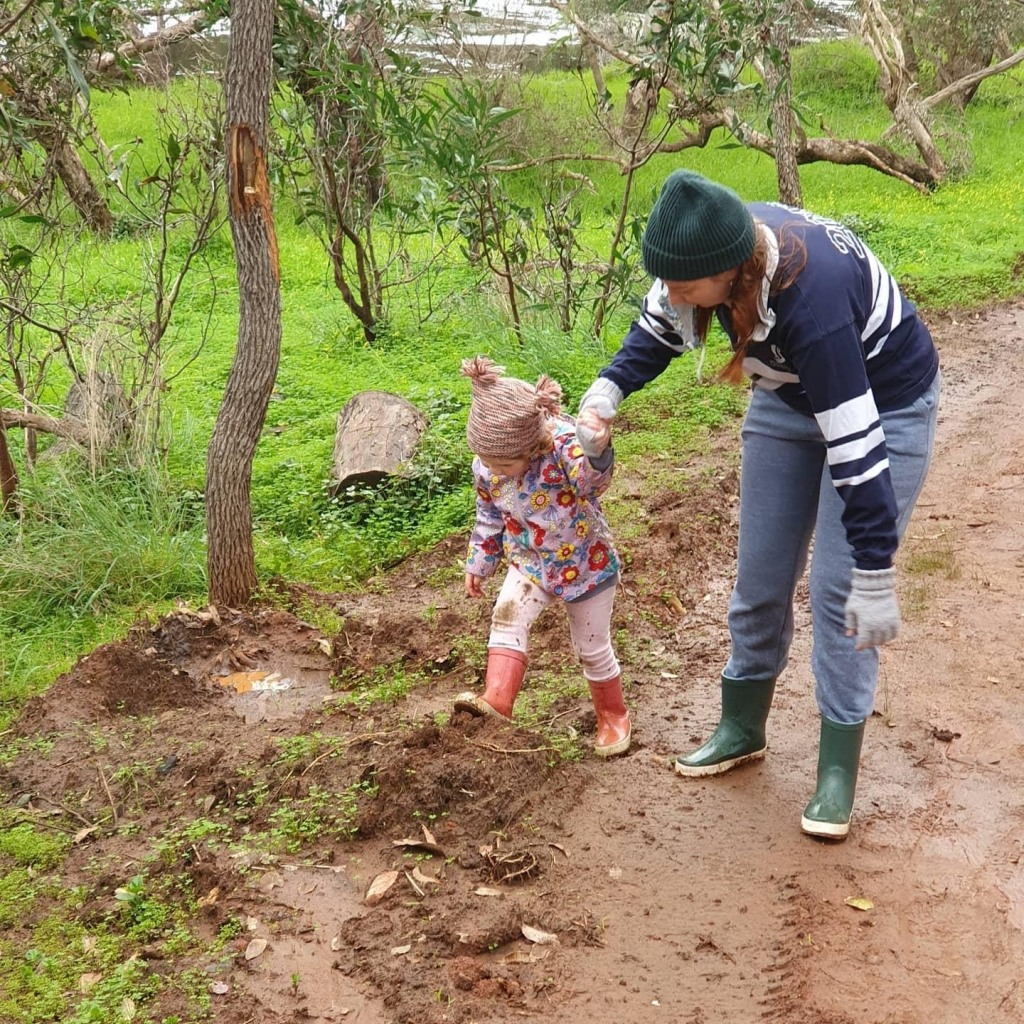 A three year old girl wearing a bright, flowery pink raincoat, pink leggings, pink gumboots and a woolen, bobbly beanie stomps down a muddy road whilst holding hands with a lady dressed in blue jeans, a blue and white striped jumper, a green beanie, grey gloves and green gumboots.
